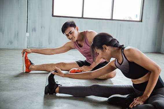 two people doing stretching before core exercise at the gym